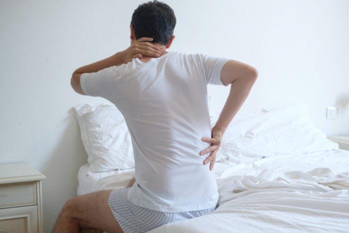 マットレスで寝ると腰と首が痛い男性